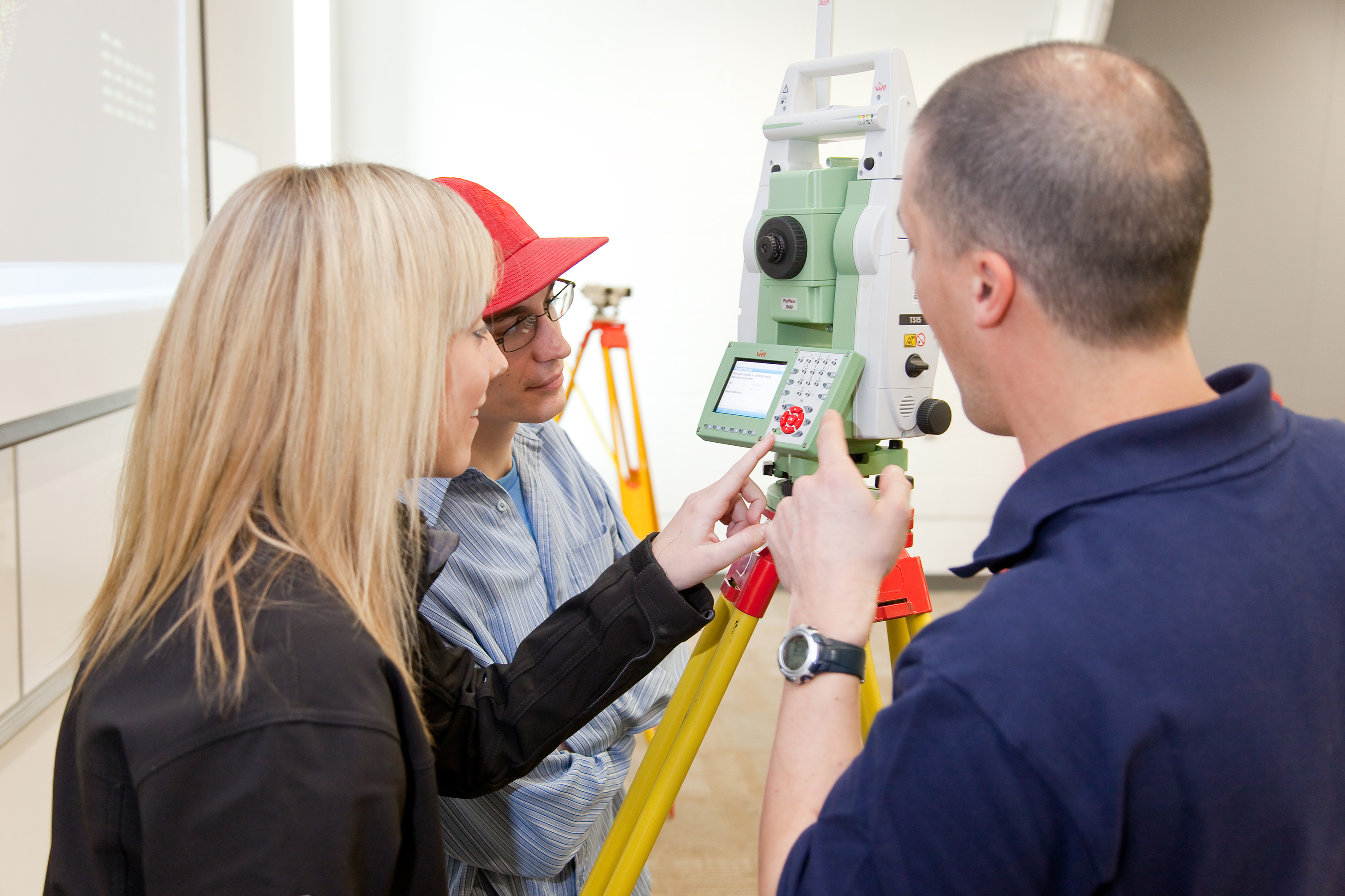 People inspecting a robotic arm